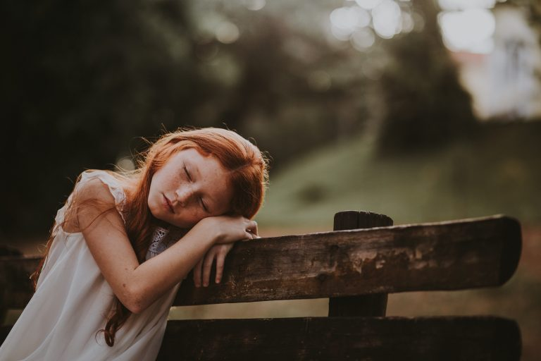 Young girl resting her head on a wooden bench