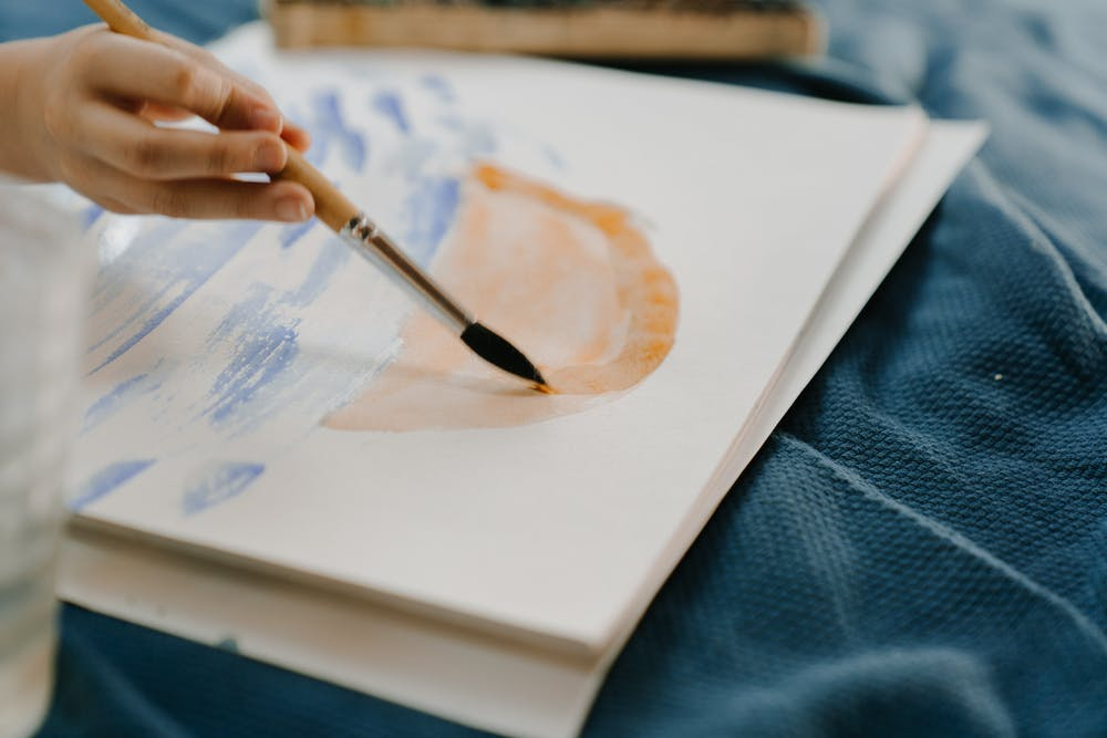 Child painting sunrise in watercolour