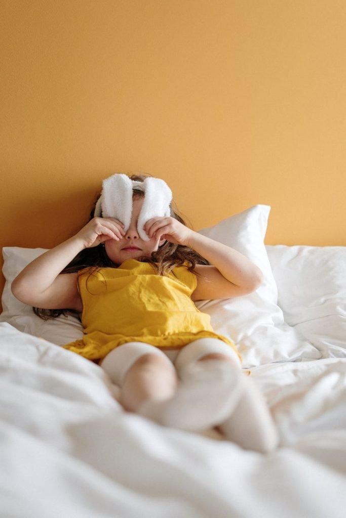 Girl with rabbit ears covering eyes from light