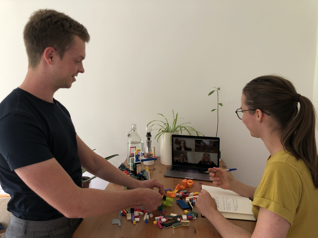 Man and woman standing at table in front of laptop for a video meeting while prototyping with LEGO