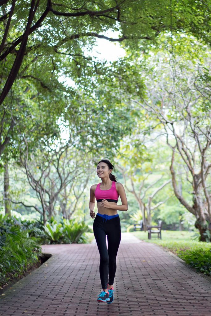 Woman smiling while jogging through a park