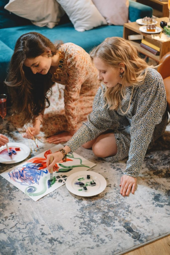 Two woman sat on floor painting together