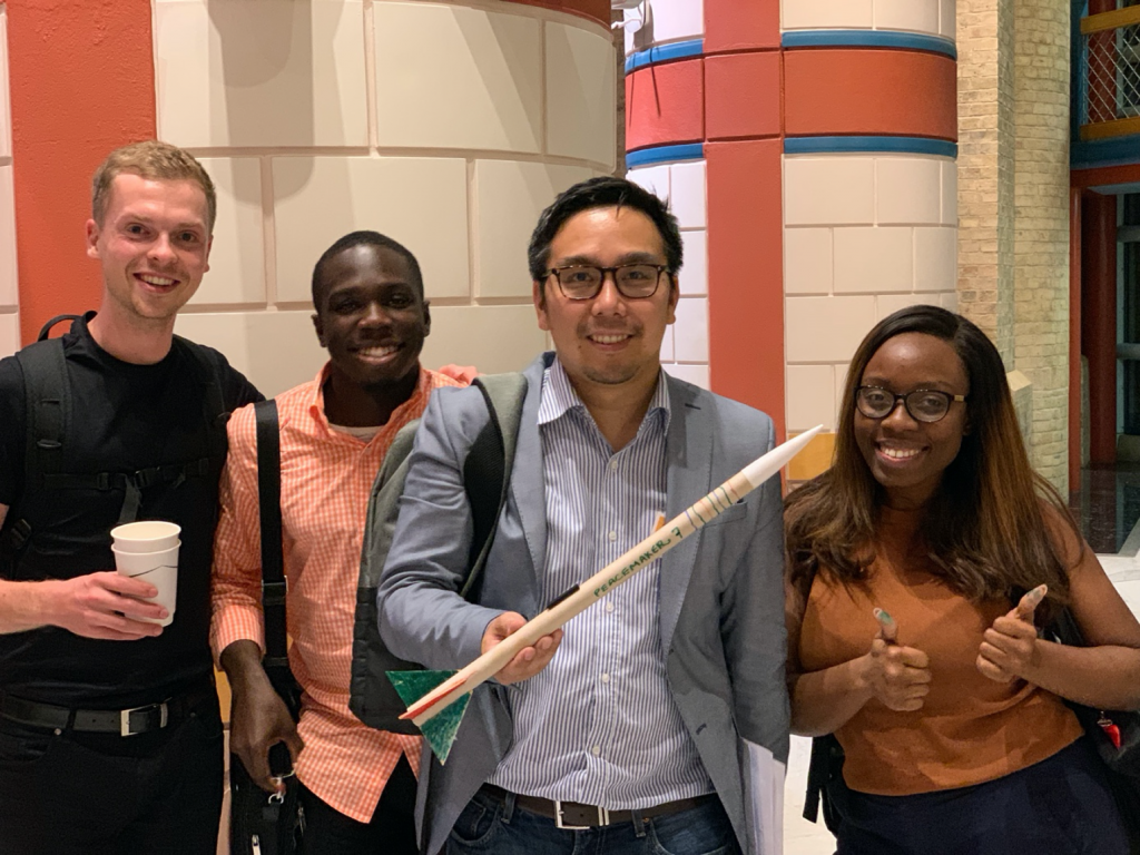 Mixed group of smiling people presenting a paper rocket