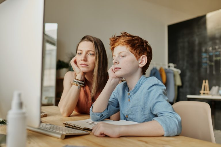 Woman and boy sitting in front of computer screen