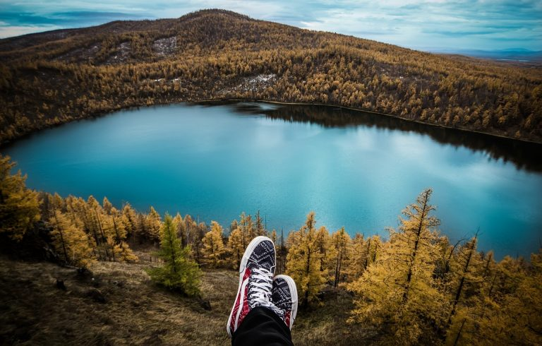 feet of person sitting on hill with view on lake