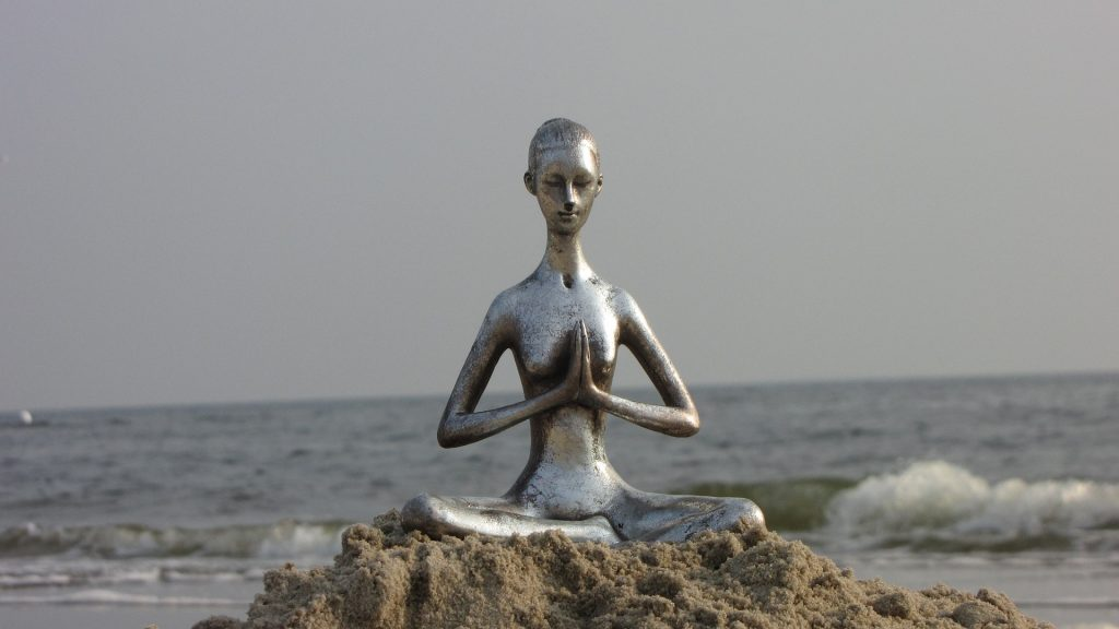 Yoga statue placed in the sand at beach